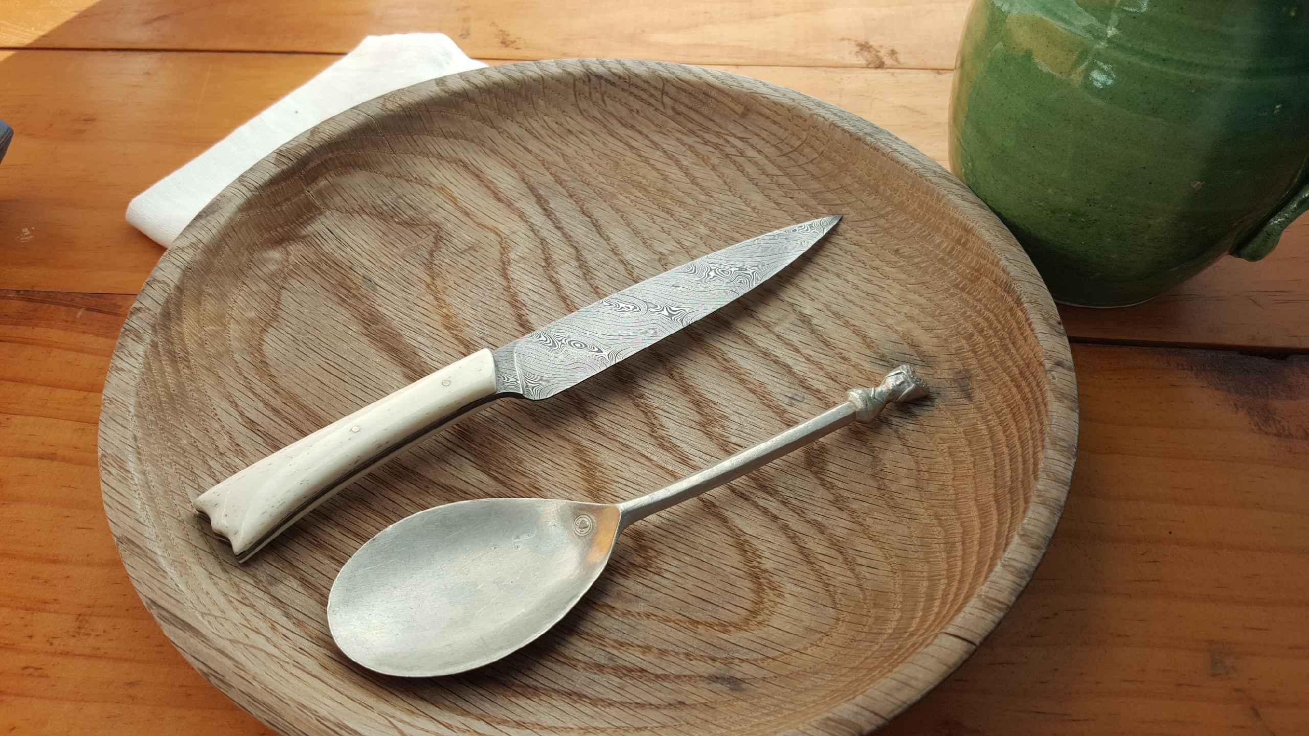 Bone handled eating knife on plate with spoon